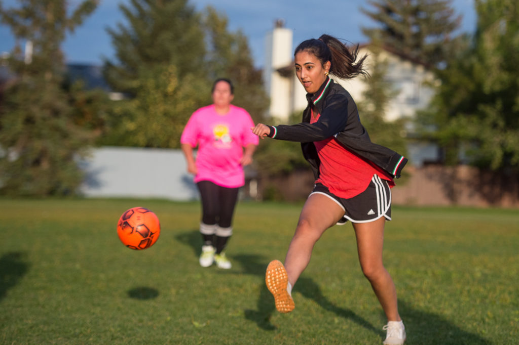 Woman in a red shirt and black shorts kicking an orange soccer ball.