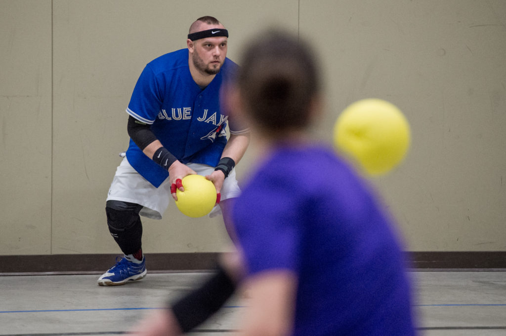 A woman throws a dodgeball at a man wearing a Blue Jays jersey.