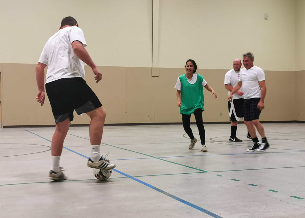 Adults playing soccer. Three men in white T-shirts and one woman wearing a green bib.