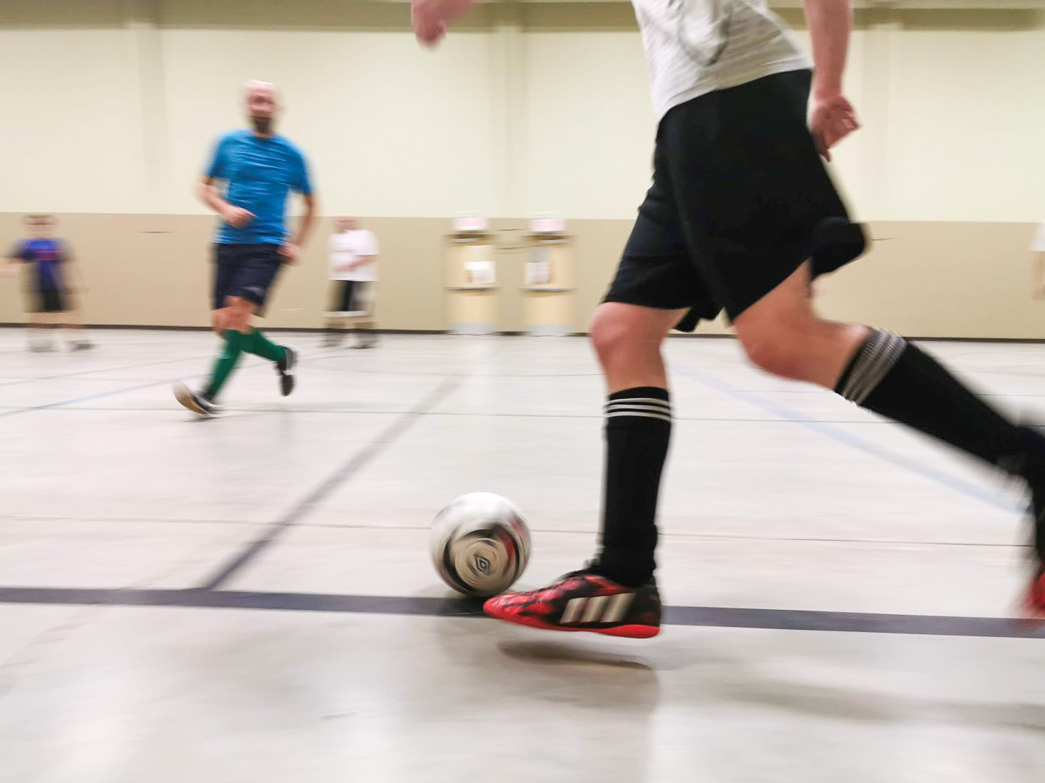 Someone dribbling a ball in indoor soccer.