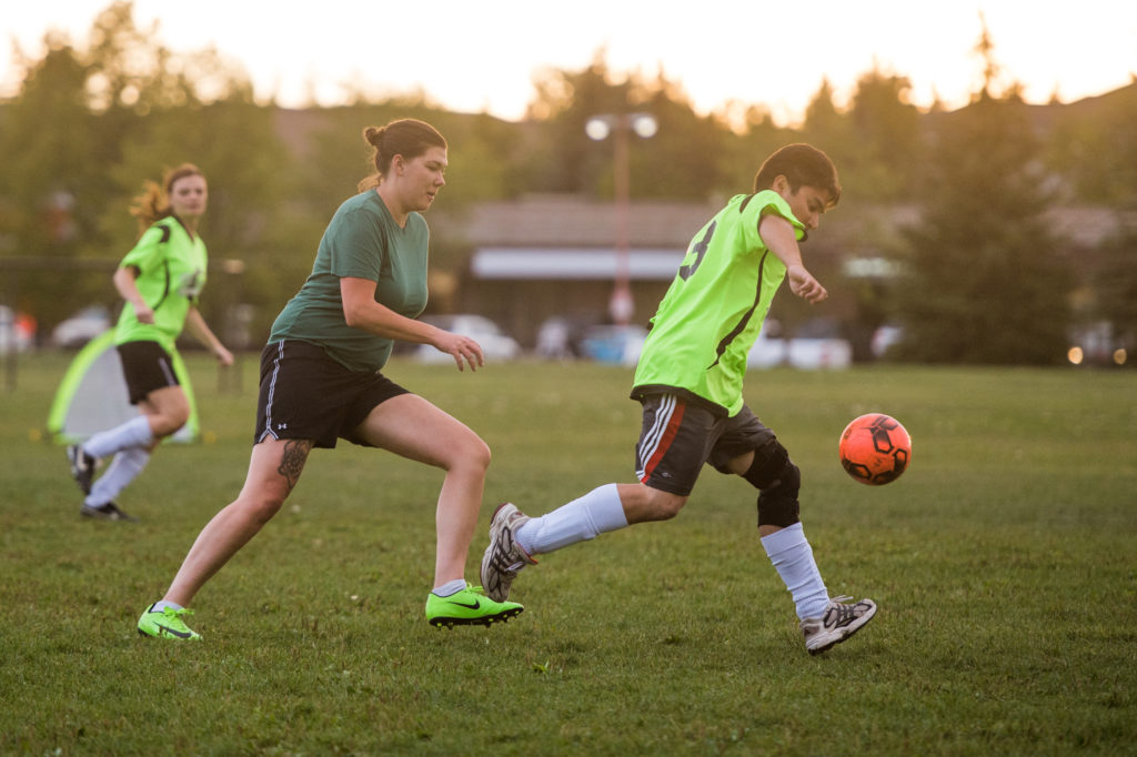 People playing soccer in Saskatoon with neon green shirts and a neon orange soccer ball.